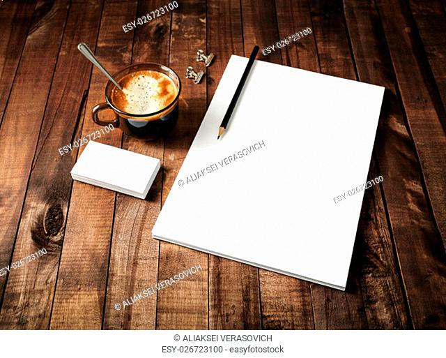 Blank paperwork template: letterhead, coffee cup and pencil on vintage wooden table background. Mock-up for ID. Blank stationery template for design portfolios