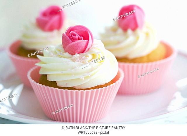Cupcakes decorated with frosting and pink wafer roses