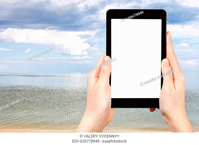 travel concept - tourist photographs of view of Azov Sea on tablet pc with cut out screen with blank place for advertising