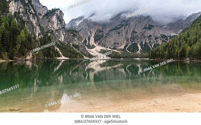 Autumn hike around the Pragser Wildsee in the Dolomites, Italy. View in direction Seekofel, summit is covered with clouds