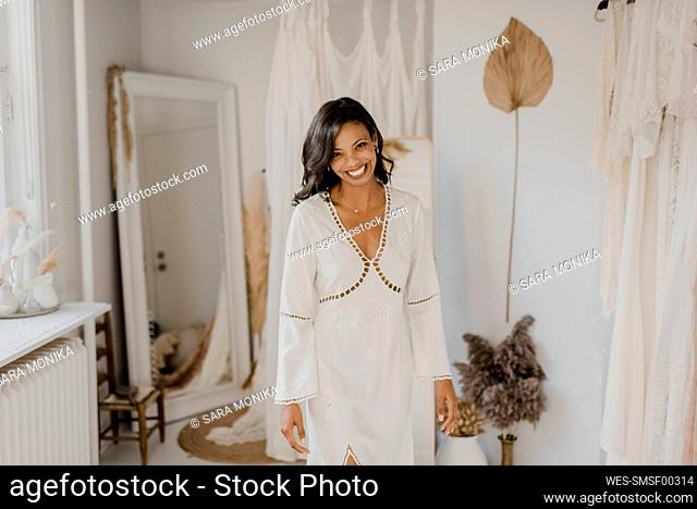 Smiling young bride standing at home