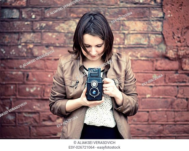 Pretty young woman holding retro camera and taking photo on vintage brick wall background. Selective focus on camera. Toned photo with copy space