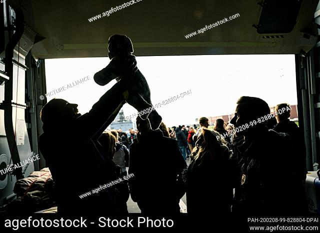 """08 February 2020, Lower Saxony, Wilhelmshaven: Daniel, a marine from the frigate """"""""Hamburg"""""""", holds his baby in his hands after his return from deployment in..."""