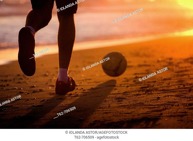 Playing the ball on the beach at sunset