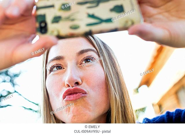 Mid adult woman posing for selfie with smartphone