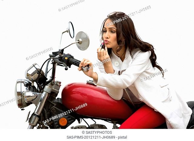 Woman applying lipstick on her lips while sitting on a motorcycle