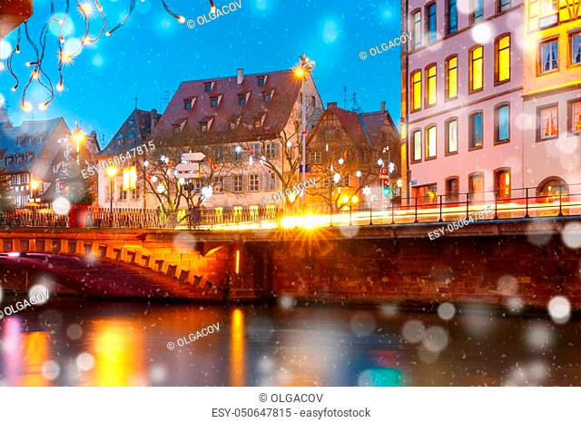 Picturesque Christmas quay with mirror reflections in the river Ile during evening blue hour, Strasbourg, Alsace, France