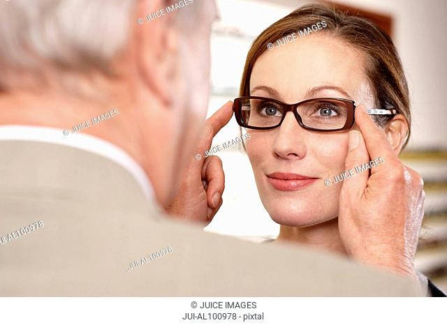 Optician adjusting eyeglasses on patient in office