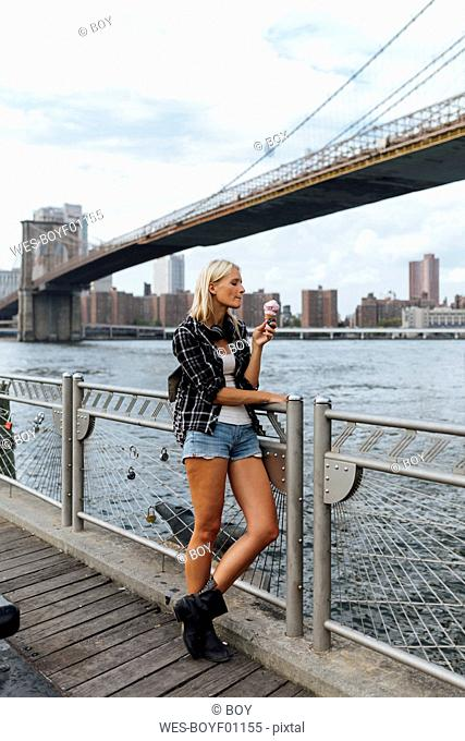 USA, New York City, Brooklyn, young woman standing at the waterfront eating an ice cream