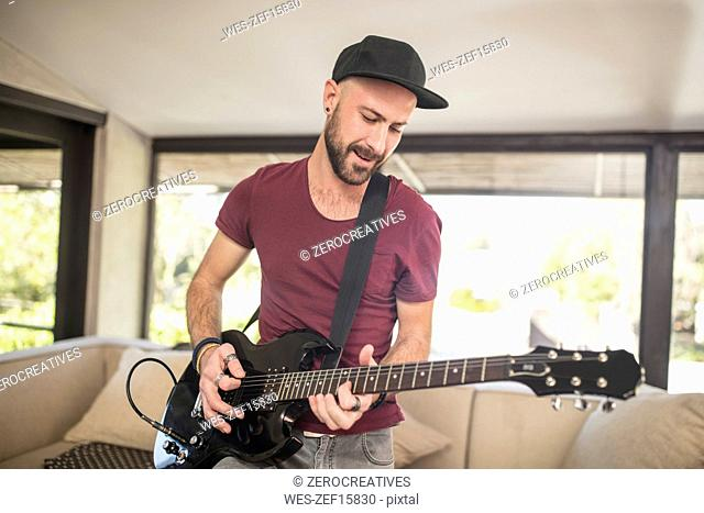 Young man playing electric guitar in living room at home