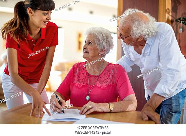 Senior woman signing a contract, nurse and senior man helping her