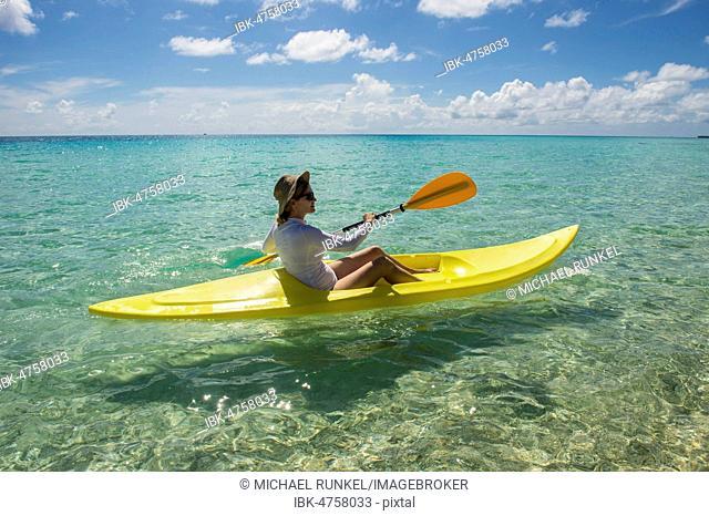 Female tourist kayaking in the turquoise waters of Tikehau, Tuamotu Archipelago, French Polynesia