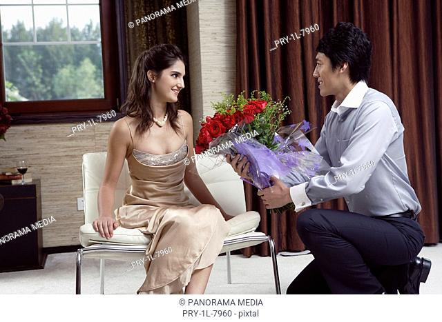 Young man giving flowers to young woman