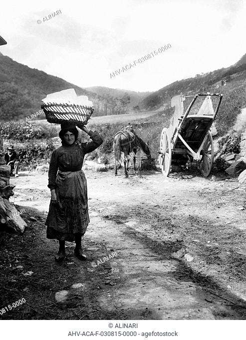 A female ice worker of Maladrone, on the Pistoian Apennines, carrying a large block of ice on her head. On the right is a horse and cart, shot 1915 ca