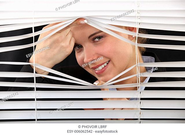 woman looking through the blinds