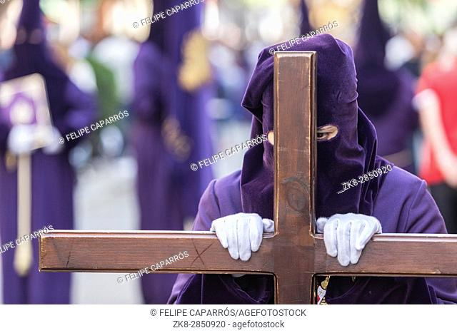 Penitent dressed in purple tunic of velvet resting on wooden cross during atonement station on Holy Week, Andalusia, Spain