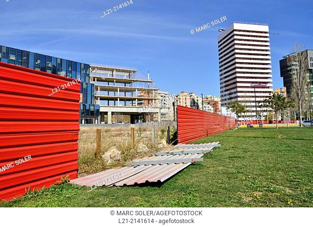 Fallen red aluminium wall, green grass, wasteland, fence, office buildings, blue sky. Plaça Europa, Plaza Europa, District VII, Gran Via
