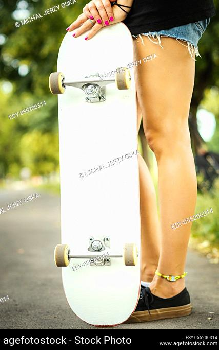 girl with a white skateboard stands and poses on a summer day