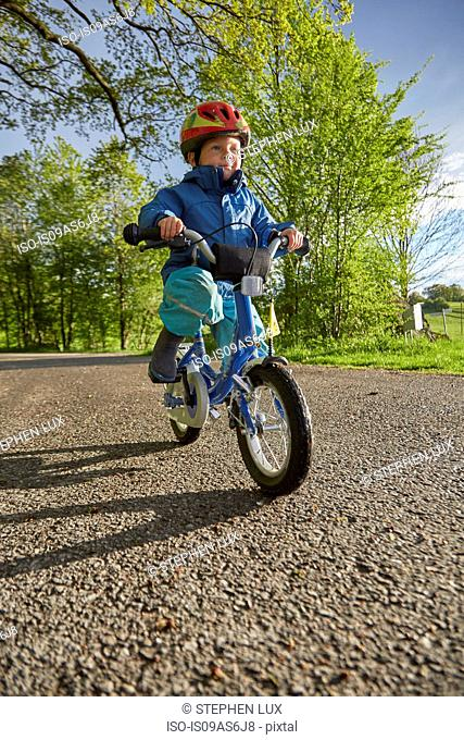 Boy wearing red cycle helmet cycling on rural road