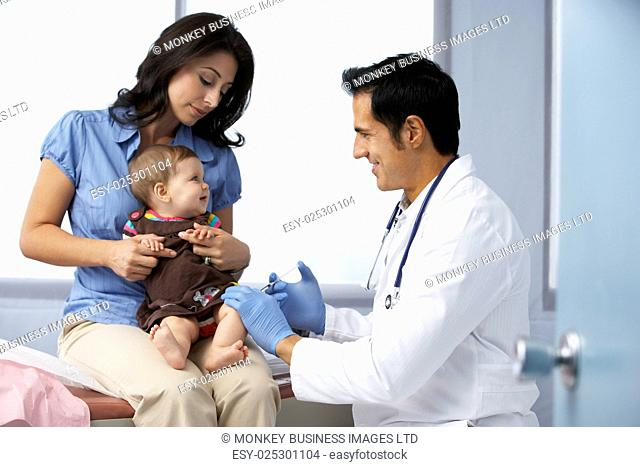 Doctor In Surgery Examining Baby Girl