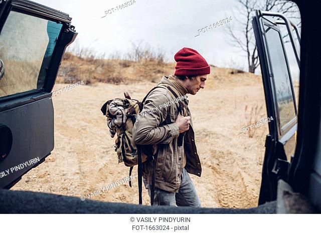 Side view of man carrying backpack while walking in forest seen through open vehicle trunk