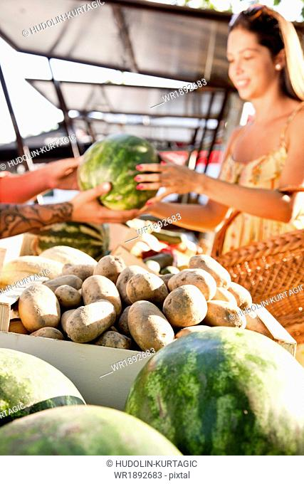 Young woman buying watermelon at market stall
