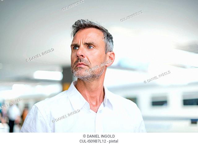 Mature businessman looking back from train station platform