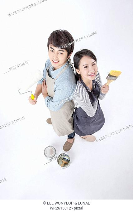 Smiling young couple with paint brushes and rollers