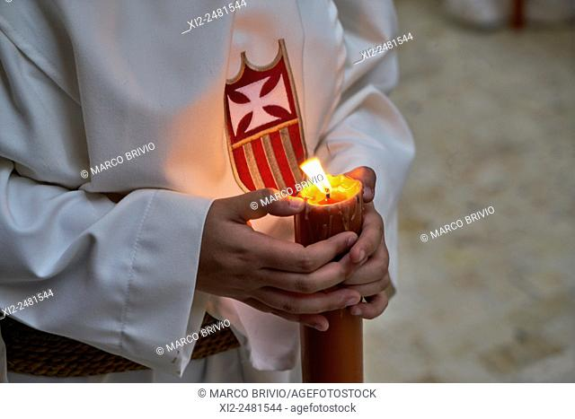 Malaga: religious processions during the Holy Week. Penitents bearing candles. Spain