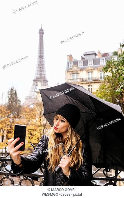 France, Paris, young woman taking a selfie with the Eiffel Tower in the background
