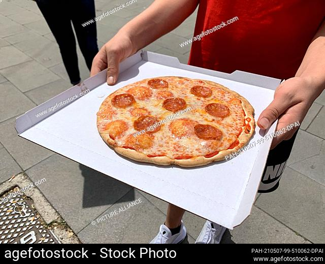 """07 May 2021, Italy, Rom: A man shows a pizza purchased from the """"""""Mr. Go"""""""" vending machine. In Italy's capital Rome, """"""""Mr"""