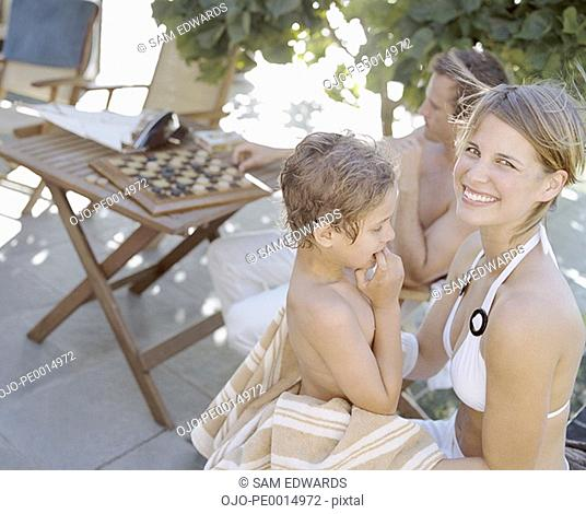 Woman drying boy with towel outdoors