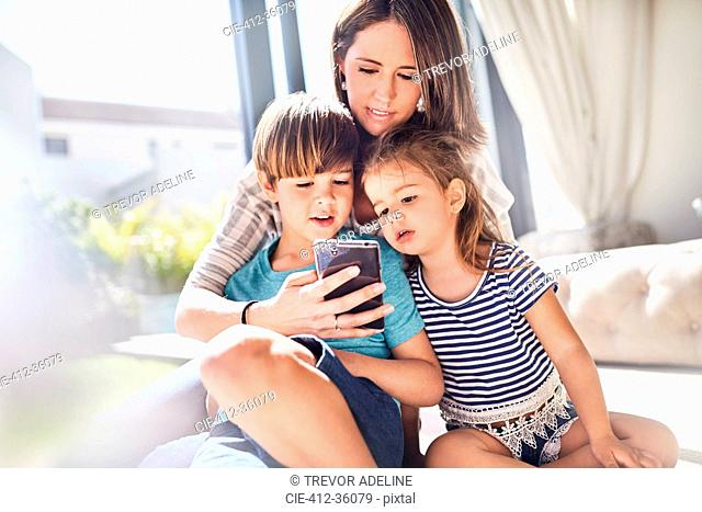 Mother and children using cell phone in sunny living room