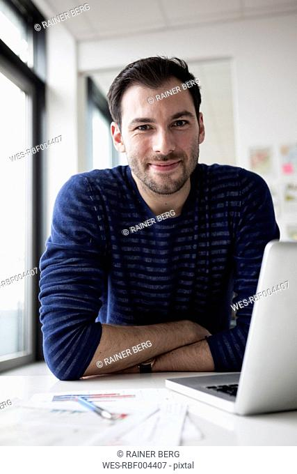 Young man sitting in office using laptop