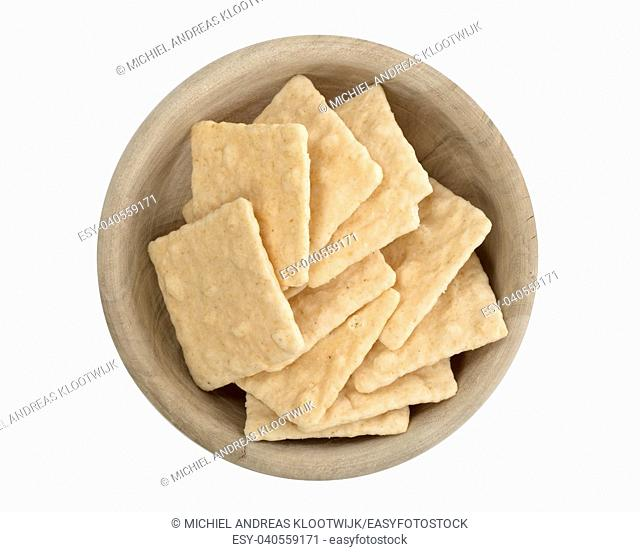 Simple crackers in a wooden bowl, isolated on a white background