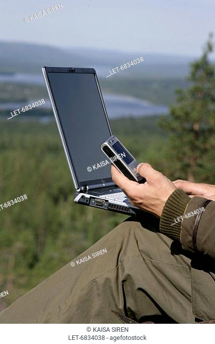 Man with cell phone and laptop computer in the wilderness  Finland