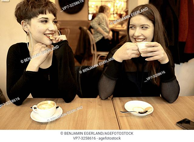 two women smiling at each other while enjoying coffee and biscuit in café restaurant, afternoon coffee break, in Germany