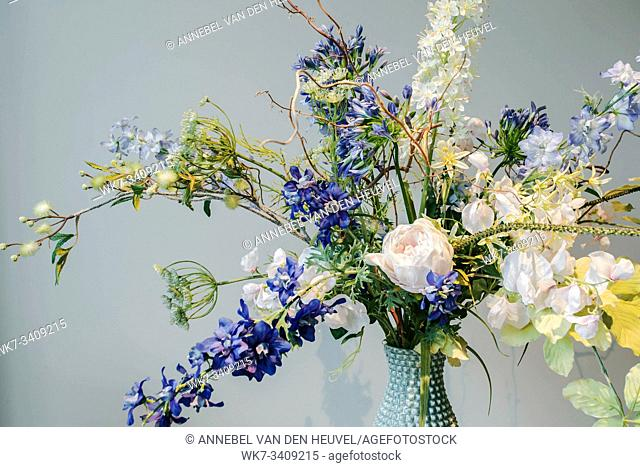 Colorful Fake flowers in a vase on the table colorful green and blue background texture, modern design beauty interior decoration