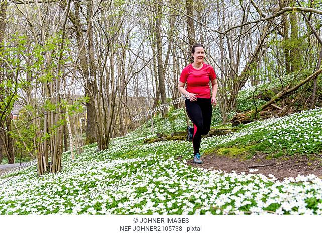Woman running in spring forest