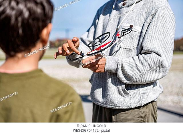 Father and son flying drone