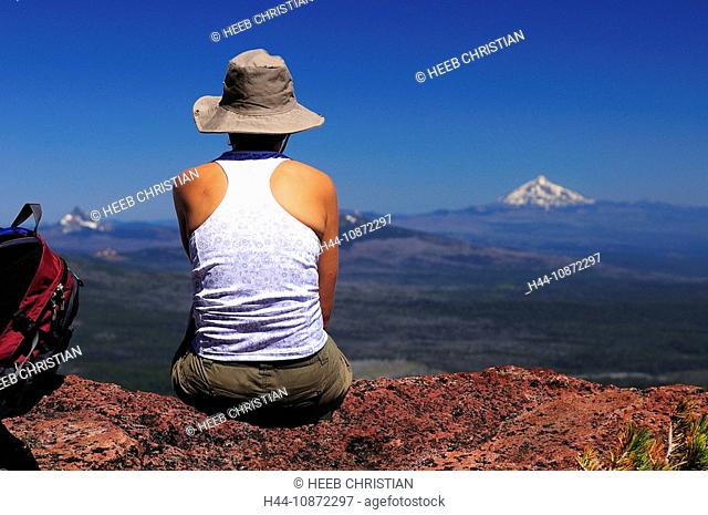 Hiker sitting at Broken Hand, view to Cascade Mountain Range, Deschutes National Forest, Sisters, Central Oregon, Oregon, USAThree Sisters Wilderness