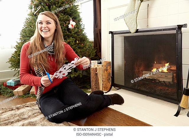 Young woman cutting out snowflake decorations at christmas