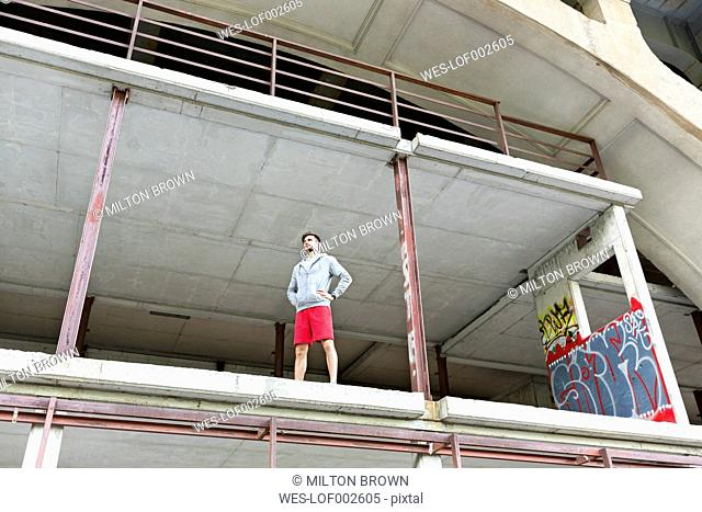 Young athletic man standing at shell of building