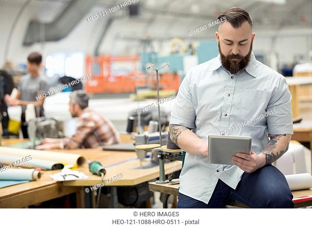 Worker using digital tablet in textile manufacturing plant