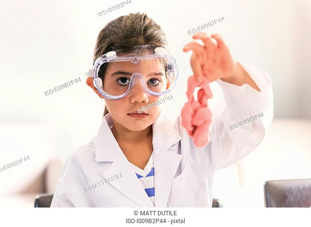 Girl wearing safety goggles holding up slime from history set
