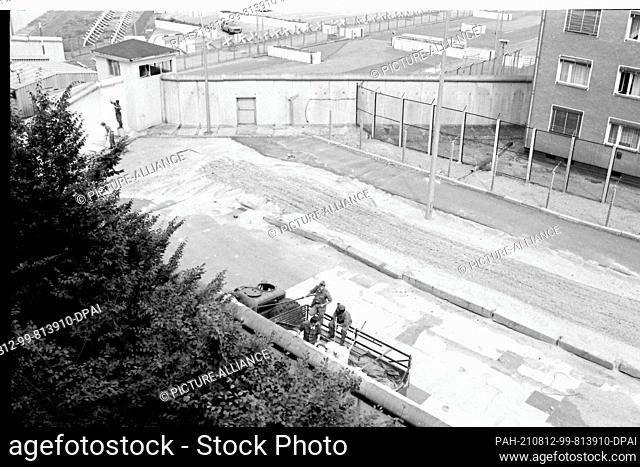 08 August 1985, Berlin: GDR border guards paint the wall at Sebastianstraße in the Kreuzberg district with white paint. In the background is the...