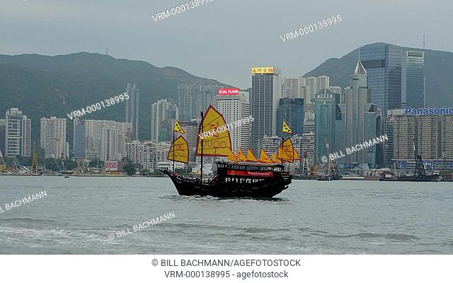 Hong Kong China skyline from water with traditional junk boat with yellow sails advertising against city background