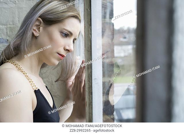 Portrait of a beautiful blond woman looking out of the window
