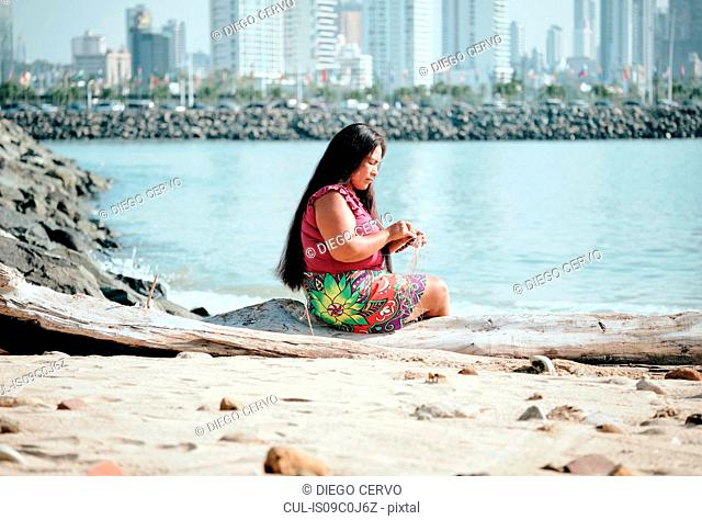 Indigenous woman weaving on beach, Ciudad de Panamá, Panama
