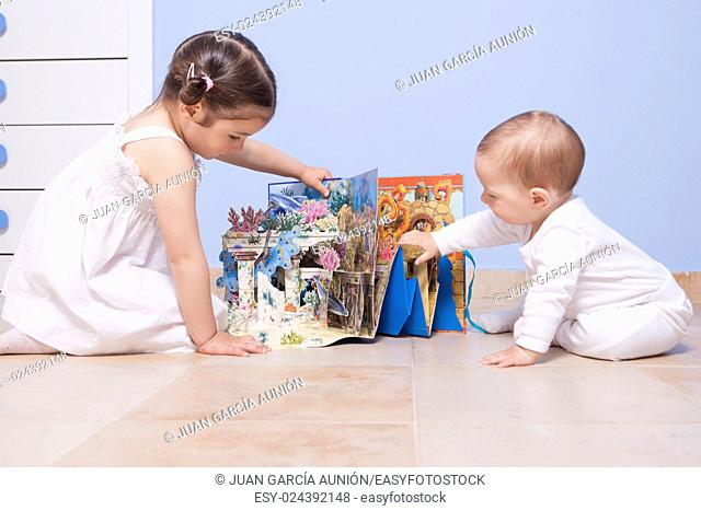 Baby boy and sister playing at toys room with pop up book